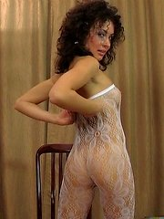 Smiley curly-head teasingly shows her goodies thru white lacy and nude hose