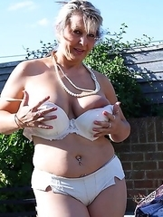 Busty mature lady strips in her garden